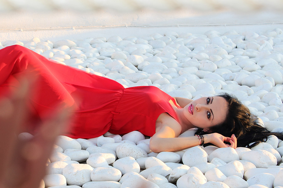 wearing a red gown with back laid and lying on white stones