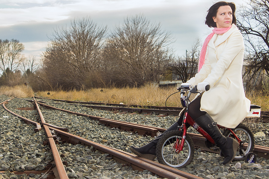 Attractive woman riding a child bike in the railways