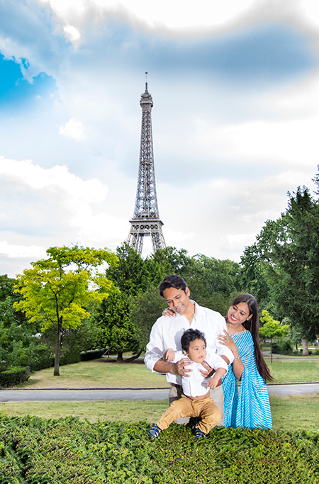 little boy with his parents in front of the eiffel tower