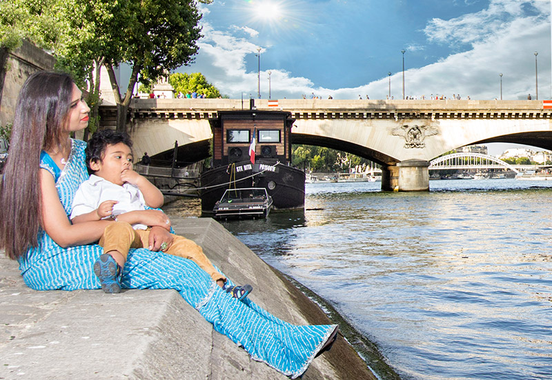 Hindu mother with traditional sari holding boy at the arms at River Seine in France