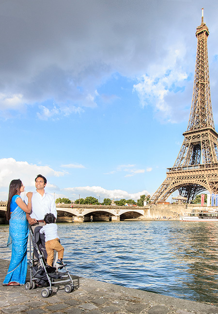 family walk across the Seine River admiring the tower of Eiffel