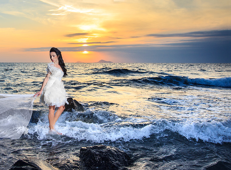 bride walking on the sea during sunset illusion