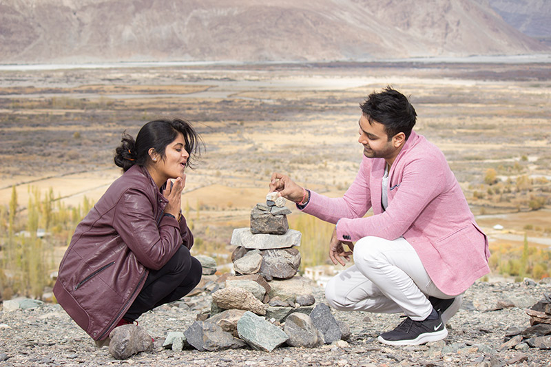 Indian couple having a good time playing with rocks