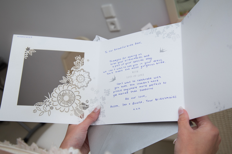 bridesmaids touching letter to bride
