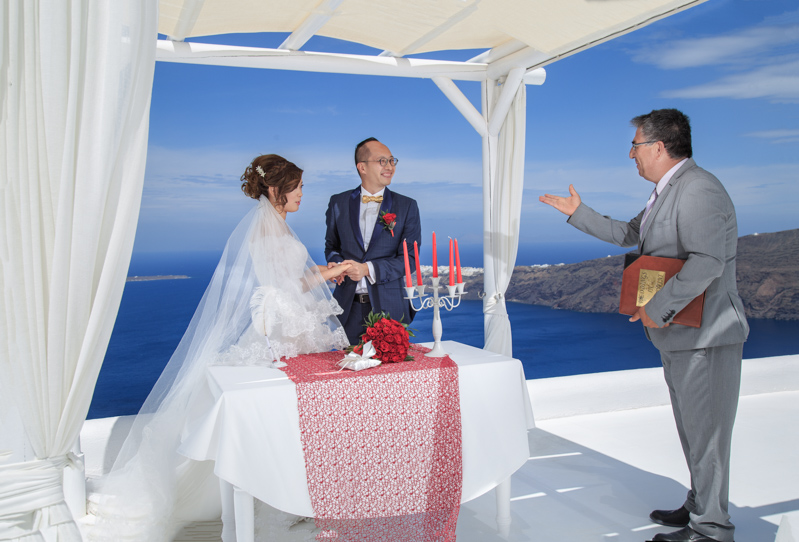 Wedding officiant pronounces husband wife in Santorini Photographer