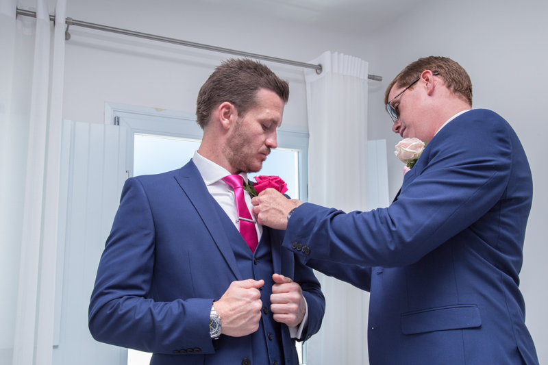 groom is getting ready with best man assistance