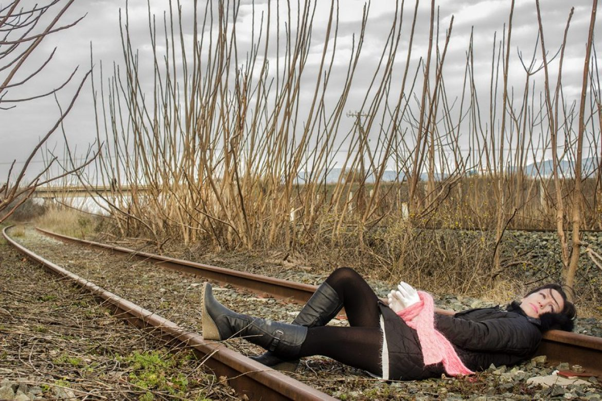 An attractive woman in an abandoned railway graveyard – Childhood revisited